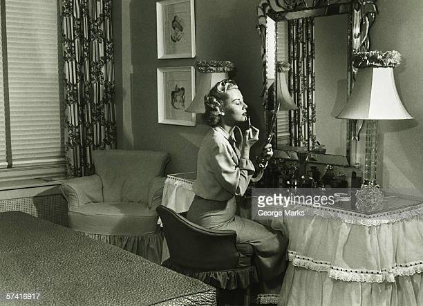 Woman applying lipstick at vanity table, (B&W)