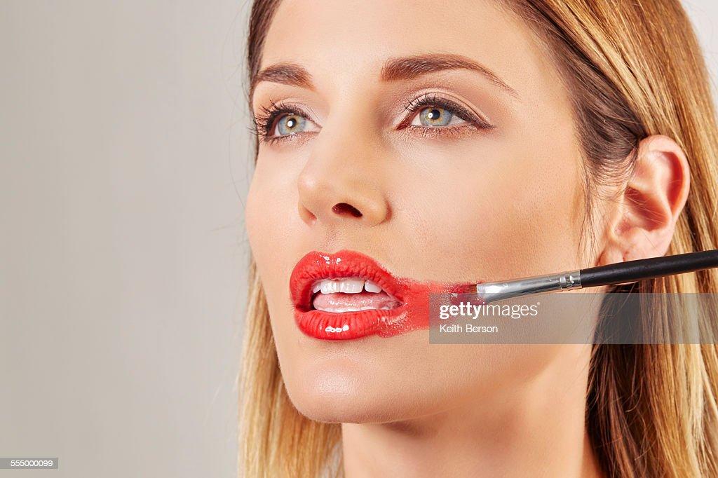 Woman applying lipstick badly
