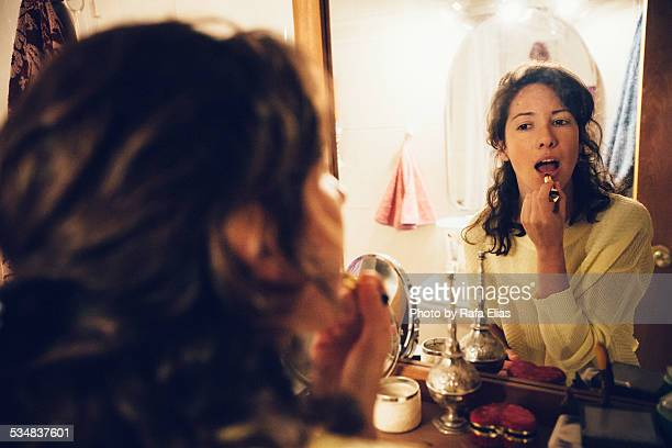 Woman applying lipstick in bathroom mirror