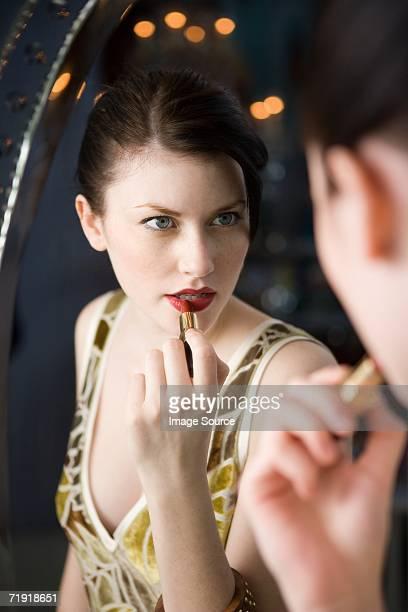 Femme appliquant du rouge à lèvres devant un miroir