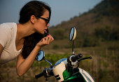 Woman applying lipstick in wing mirror of moped