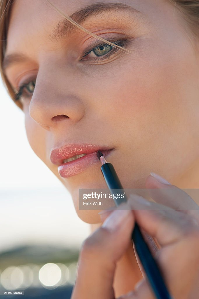 Woman applying lipstick : Foto stock