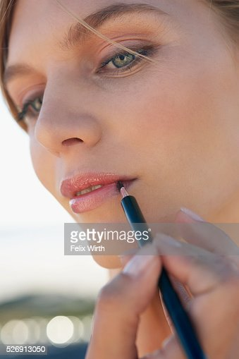 Woman applying lipstick : Stockfoto