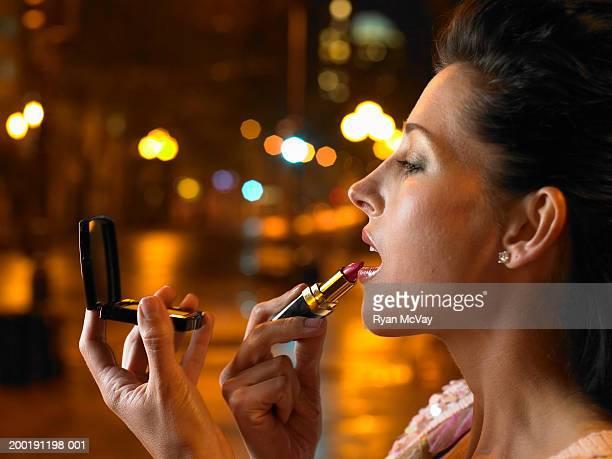 Woman applying lipstick, profile, close-up