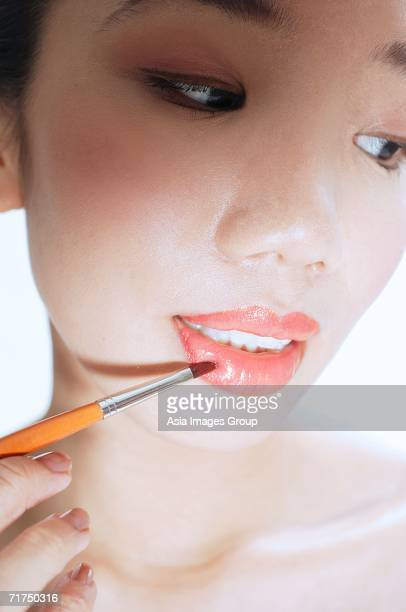 Woman applying lipstick with lip brush