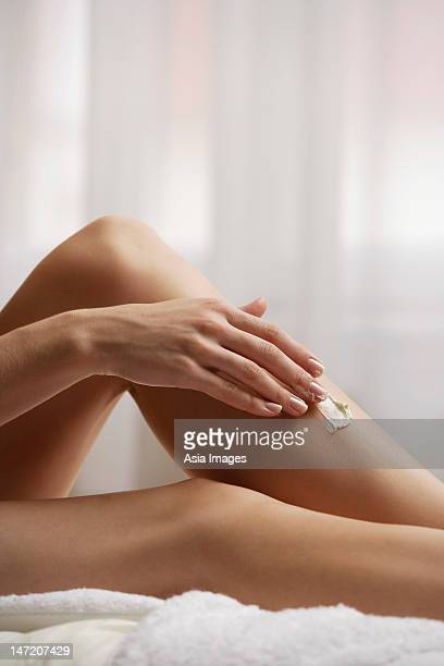 woman applying lotion to legs