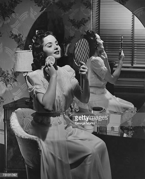 Woman applying make up at vanity table (B&W),
