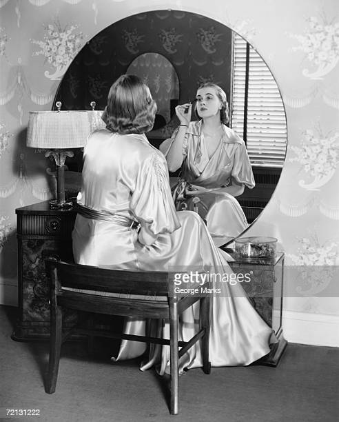 Woman applying make up in front of vanity table,  (B&W),