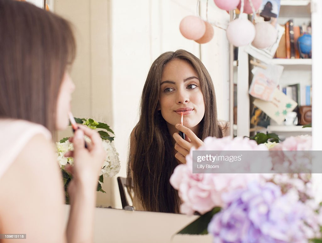 Woman applying make up in mirror