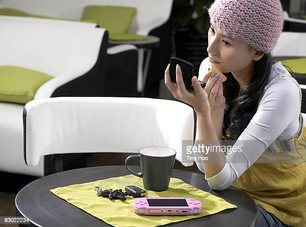 Woman applying makeup in cafe
