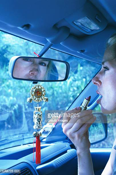Woman applying make-up in car, close-up