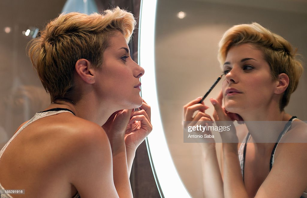 Woman applying makeup in mirror