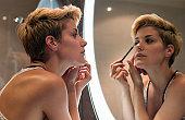 Woman applying makeup in mirror