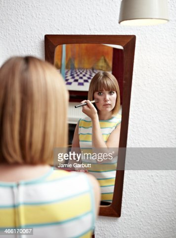 Woman applying make-up in retro-styled mirror. : Stock Photo