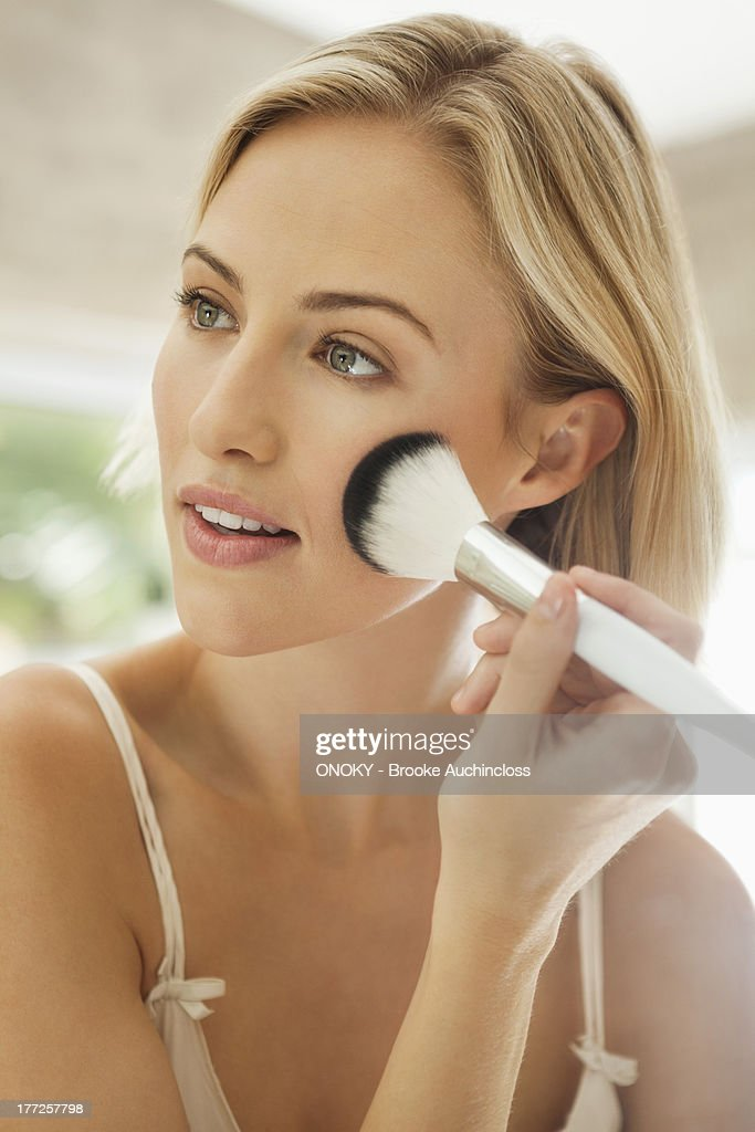 Woman applying make-up with a brush