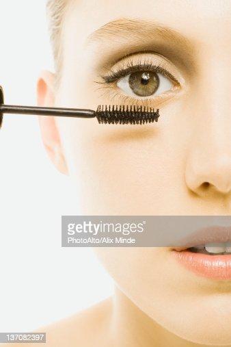 Woman applying mascara, close-up