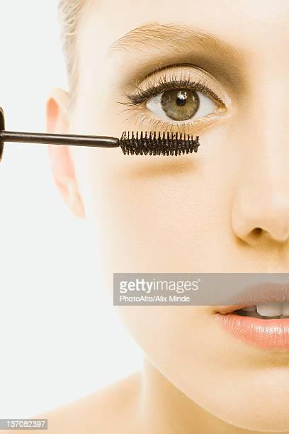 Woman applying mascara, close-up