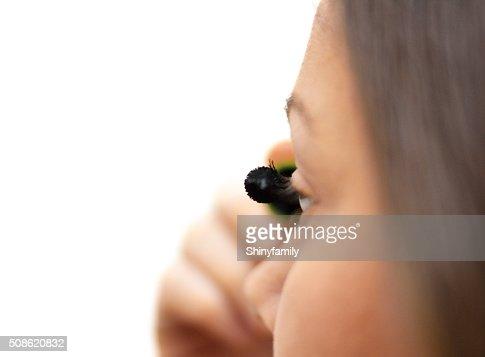 Woman applying mascara on eyelashes : Stock Photo