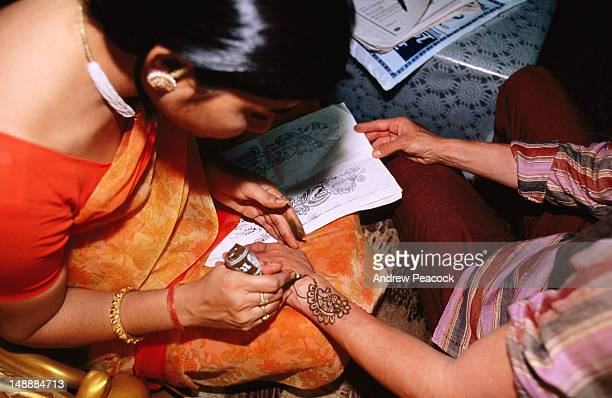 Woman applying Mehendi application.