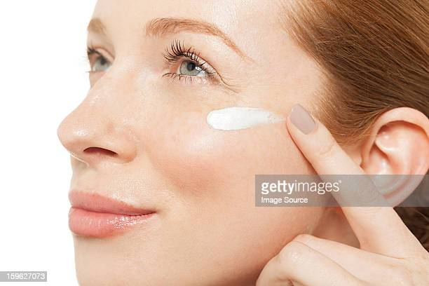 Woman applying moisturiser