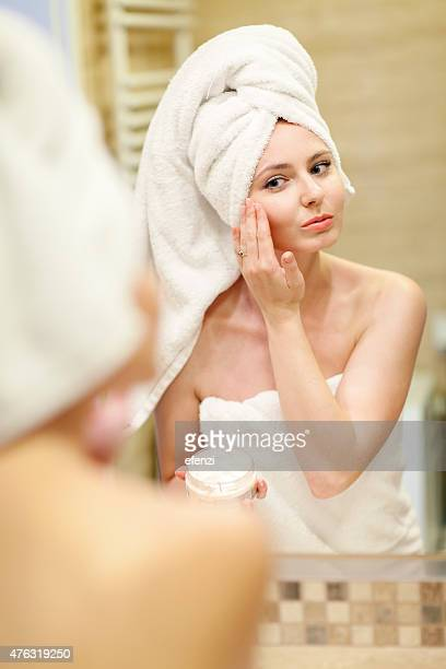 Woman Applying Moisturizer In Bathroom