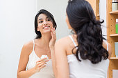 Woman caring of her beautiful skin on the face standing near mirror in the bathroom. Beautiful young woman applying moisturizer on her face. Smiling girl holding little jar of skin cream and applying