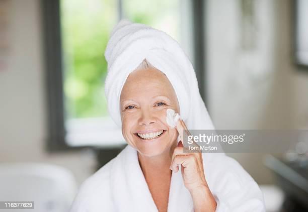 Femme application de crème hydratante sur le visage
