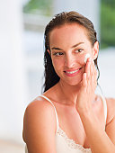 Woman applying moisturizer to face