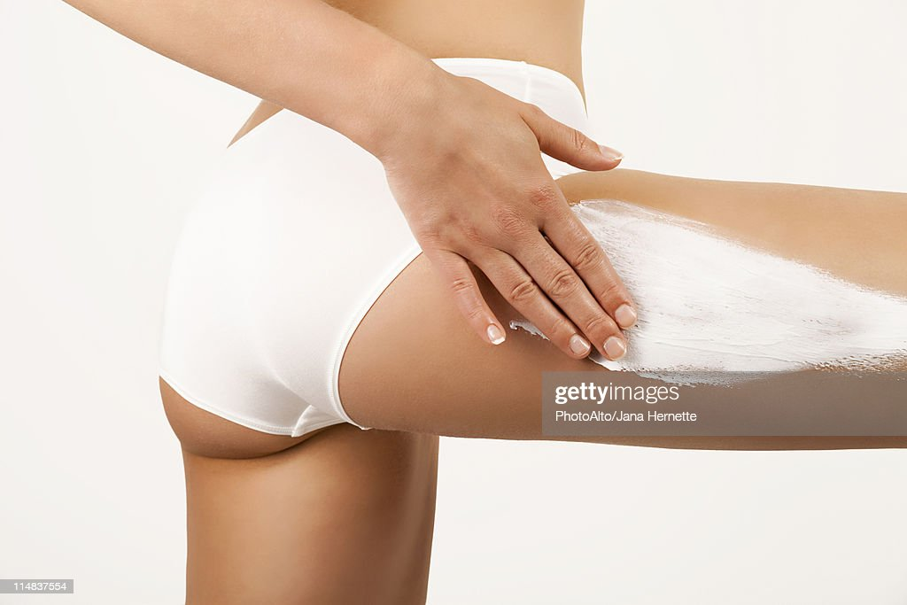 Woman applying moisturizer to thigh, cropped