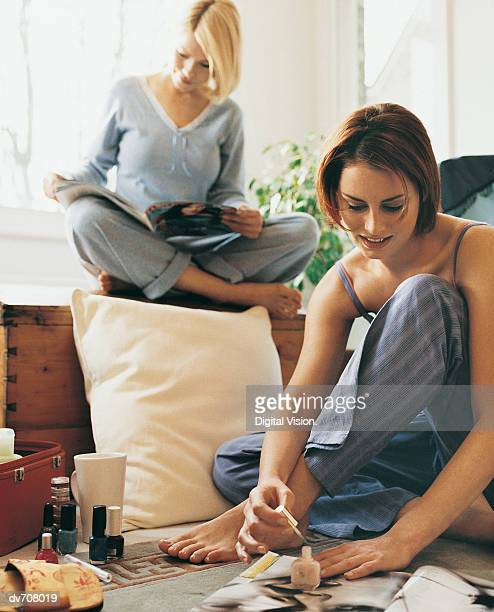 Woman Applying Nail Varnish with Female Friend Reading a Magazine