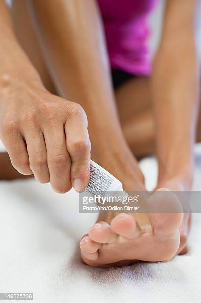 Woman applying ointment to foot, cropped