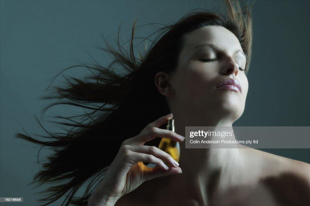 Woman applying perfume : Stock Photo
