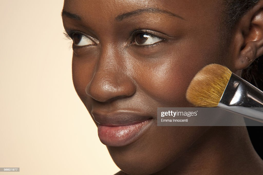 Woman applying powder on chick, looking up smiling : Stock Photo