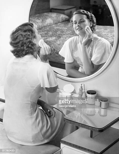 Woman applying powder with powder puff in front of mirror, (B&W)