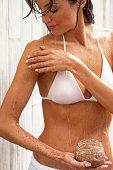 Woman applying scrub to body, close-up
