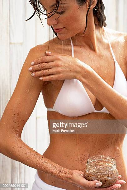 Woman applying scrub to body, close-up
