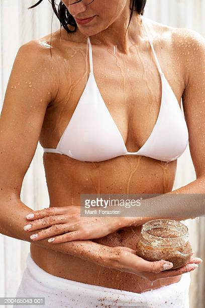 Woman applying scrub to body, mid section, close-up