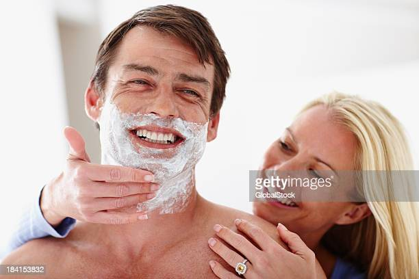 Woman applying shaving cream on man's face