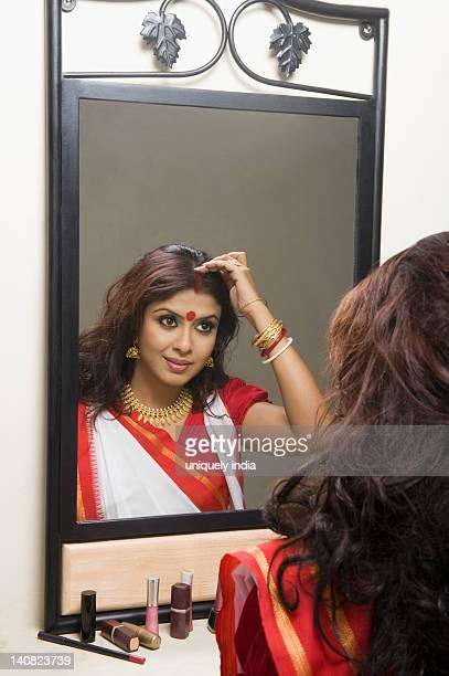 Woman applying sindoor on her head