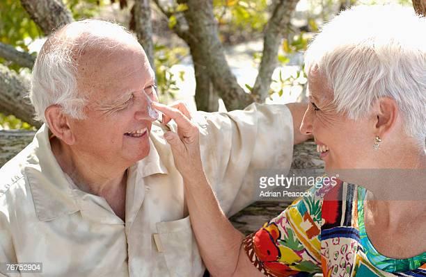 Woman applying sun block to mans nose