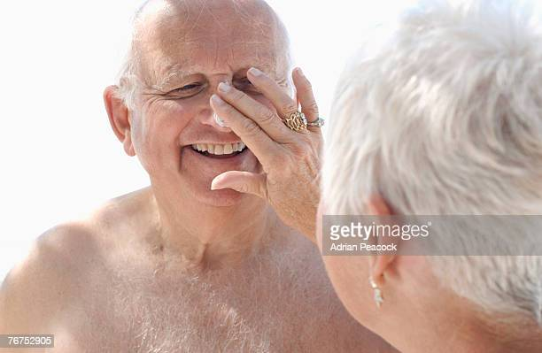 Woman applying sunblock to mans nose