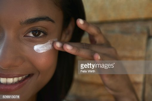 Woman applying sunscreen : Bildbanksbilder