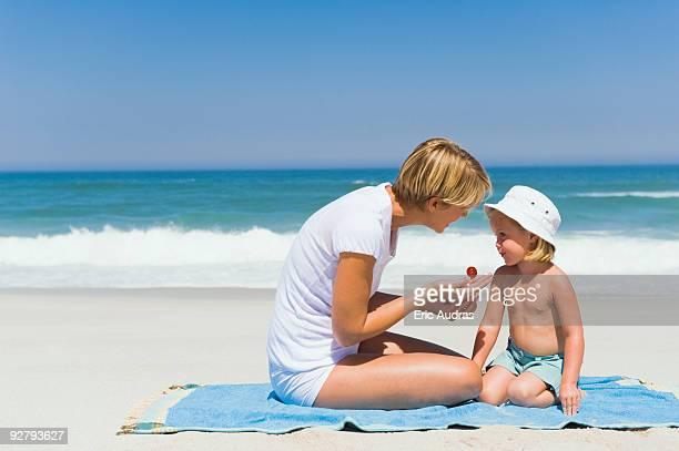 Woman applying suntan lotion on her daughter on the beach