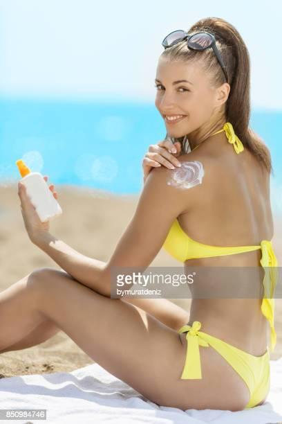 Frau benutzt Sonnencreme