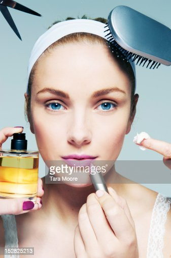 woman applying various beauty products to face
