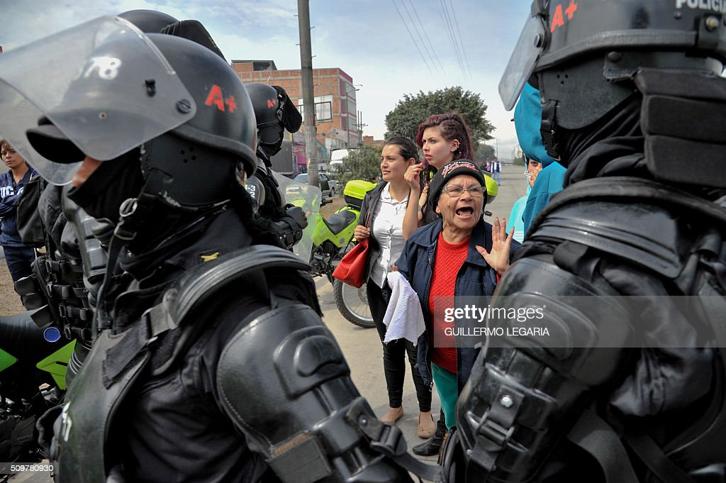 A woman argues with riot police during a protest at the 'Transmilenio' station in southern Bogota, Colombia, on February 12, 2016. Users of public transportation blocked roads to protest what they consider poor service and high cost. Amid the protest several buses were damaged as well as stations destroyed and several demonstrators were detained by police after clashes. AFP PHOTO / GUILLERMO LEGARIA / AFP / GUILLERMO LEGARIA