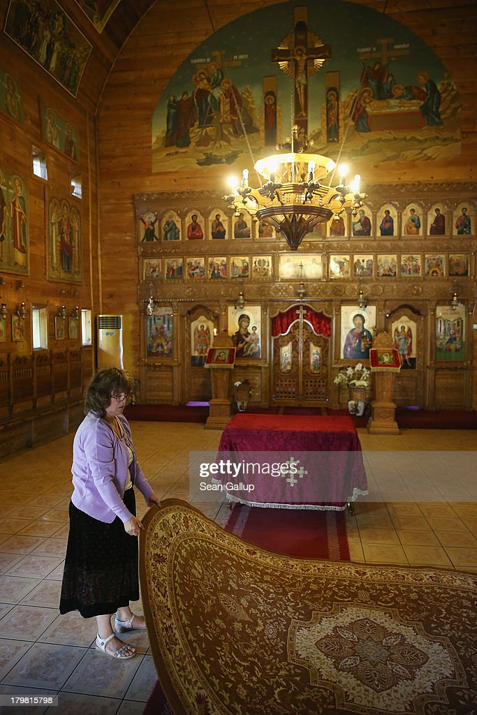 A woman arranges a carpet after a cleaning lady mopped the floor at the wooden church at Titan park on September 7, 2013 in Bucharest, Romania. The church, called the Biserica Pogorarea Sfantului Duh, was built in the 1990s. While Romania's economic output has risen significantly since it joined the European Union in 2007, it still lags in infrastructure development and the fight against corruption.
