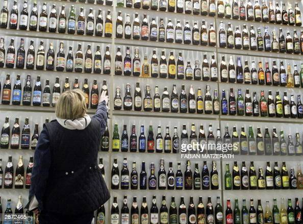 A woman arranges a shelf with hundreds of beer bottles on the stand of German Brewers federation presenting 580 brands of beer 15 January 2004 in...
