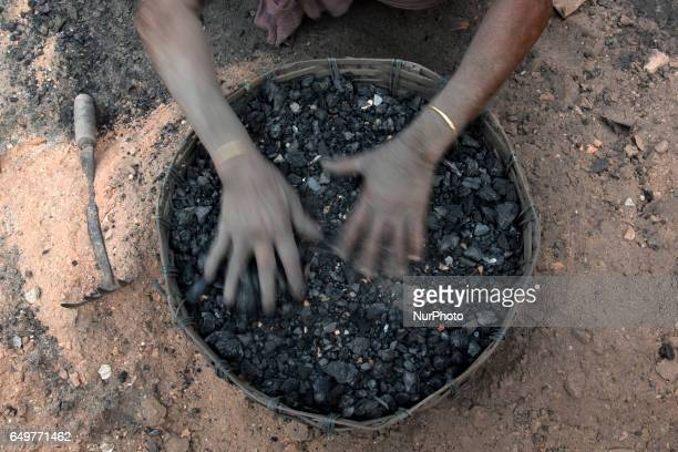 Woman arranges coal in a basket Kamduni West Bengal India 080317 The brick kilns of Bengal employ a large number of laborers from distant villages of...