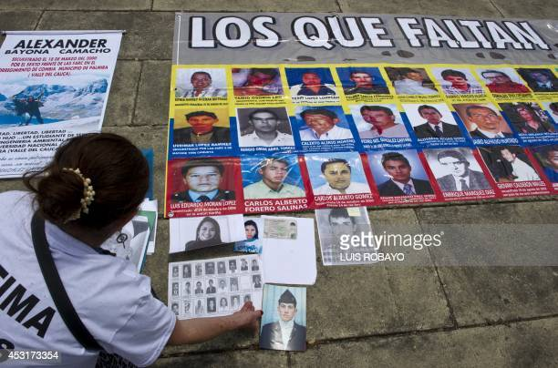 A woman arranges posters in support of victims of the FARC guerrillas during the National Forum for Victims focus on the victims of the armed...